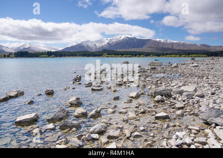 Ruataniwha Inlet foreshore at low tide with snow on top distant mountains under dramaitc clouds at Collingwood, Tasman Bay New Zealand. - Stock Photo