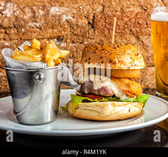 Seafood and meat burger with fried squid rings, melted cheese, crispy bacon and a beef patty served on a plate with side potato chips in a bucket. - Stock Photo