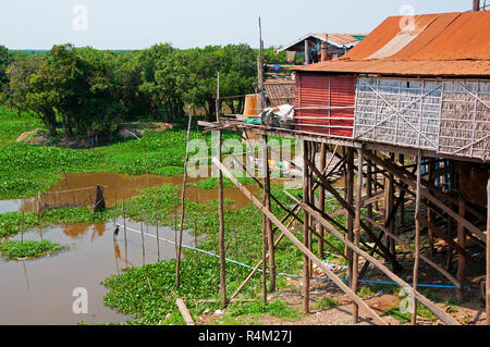 Stilt or stilted fishing village houses, in the dry season, situated on the banks of an estuary connecting it to Tonle Sap Lake,Cambodia - Stock Photo