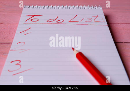 Spiral notebook with  a to-do list written with a red pencil on it, on a pink wooden table - Stock Photo