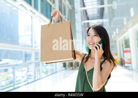 Woman holding shopping bag and talk to mobile phone - Stock Photo