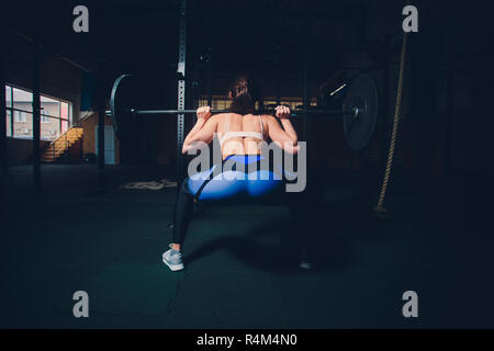 young sportswoman preparing to raise barbell in sports hall. - Stock Photo