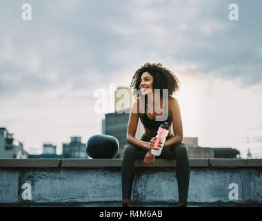 Smiling fitness woman taking rest sitting on terrace of a building during workout. Woman in fitness wear sitting on rooftop fence with a medicine ball - Stock Photo