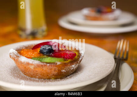 Small fruit tart on a plate and fork - Stock Photo