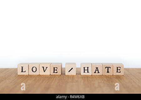 Focus on the words 'Love / Hate' made of wooden block dice with letters on a wooden table. Shallow depth of field. Copy space. - Stock Photo
