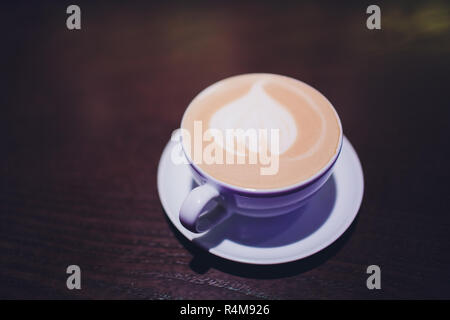 Coffee cup of Cafe' latte with heart latte art on top. - Stock Photo