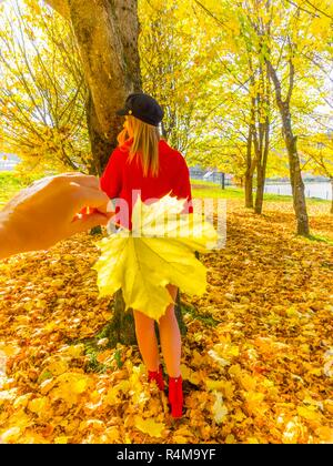 Autumn colors teen girl in woods in background behind hand holding big leaf - Stock Photo