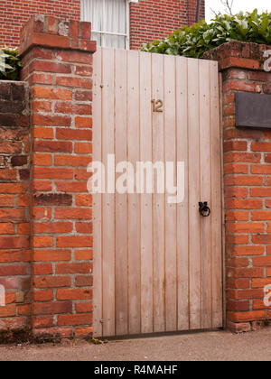 a wooden door outside closed with the number 12 on it and attached to a high wall on a house - Stock Photo