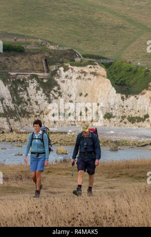 middle aged couple walking the isle of wight coastal path near the clifftop at freshwater bay on the isle of wight in the summer. - Stock Photo