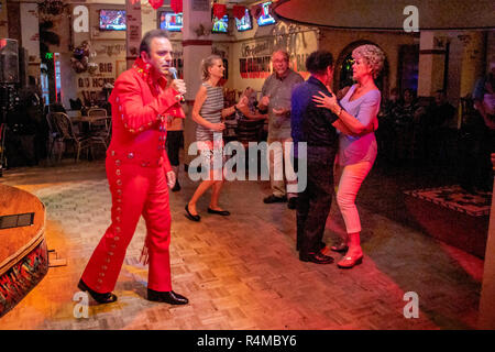 Wearing a red jumpsuit, a Middle Eastern American Elvis Presley