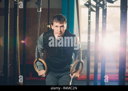Muscle-up exercise athletic man doing intense workout at the gym on gymnastic rings. - Stock Photo