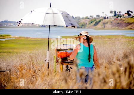 Under an umbrella in the sunshine, a female artist works on her plein air outdoor painting that matches her scenic view of Newport Beach, CA, during a timed art competition.  (Photo by Spencer Grant) - Stock Photo