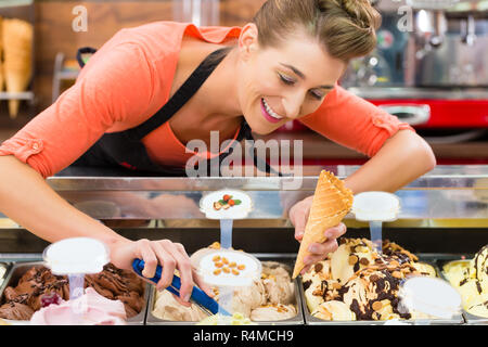 Female seller in Parlor with ice cream cone - Stock Photo