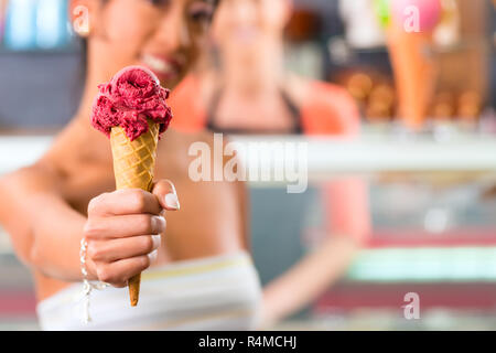 Female customer in Parlor with ice cream cone - Stock Photo