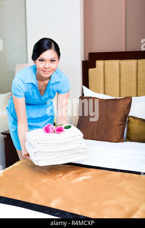 Chambermaid cleaning in Asian hotel room - Stock Photo