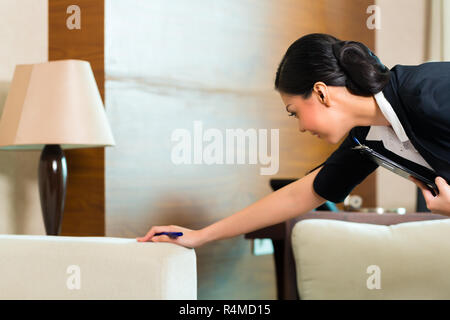 Asian Chinese housekeeper controlling hotel room - Stock Photo