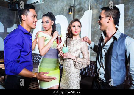 Asian young party couples drinking cocktails in club - Stock Photo