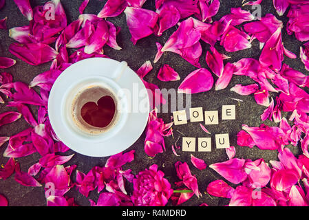 Flat lay cup of coffee with heart shape pattern and message I love you spelled in wooden blocks with purple pink peony flower petals on black backgrou - Stock Photo