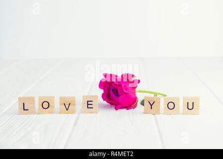Message I love you spelled in wooden blocks with pink peony bud flower on white wooden table. Love, Valentines day background. Gift, greeting, complim - Stock Photo