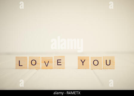 Message I love you spelled in wooden blocks standing on white wooden table. Valentines day background. Simplicity concept. Vintage tonning. Copy space - Stock Photo