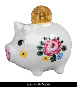cryptocurrency bitcoin laying on piggy bank - Stock Photo