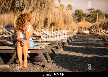 lonely beautiful middle age woman sit down on the sun beds at the beach in a summer vacation day waiting and looking enjoying the sunny season and hol - Stock Photo