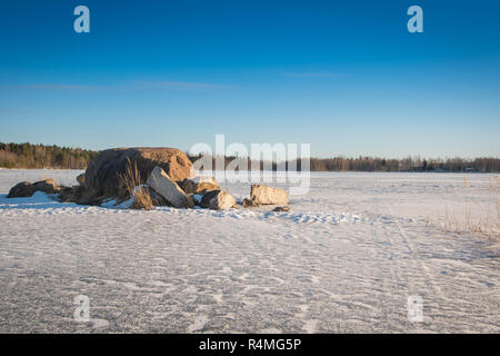 View over a frozen deep quarry lake in a sunny winter day. - Stock Photo