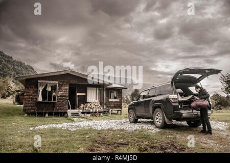 Woman on a road trip through Southern Chile unpacking her car and moving into a cabin lodge in Hornopiren. - Stock Photo