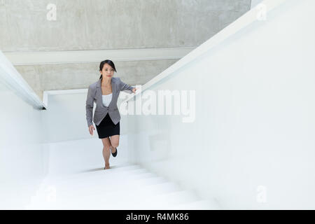 Business woman walking up to the office room - Stock Photo