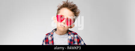 A handsome boy in a plaid shirt, gray shirt and jeans stands on a gray background. Boy in red sunglasses - Stock Photo