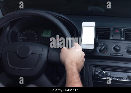 Young man using smartphone for navigation, social media or sms texting in a car. - Stock Photo