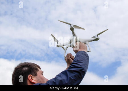 A man with a quadrocopter in his arms raised to the sky. A white drone is being prepared for the flight. - Stock Photo