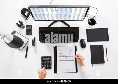 Elevated View Of A Businesswoman Calculating Invoice - Stock Photo