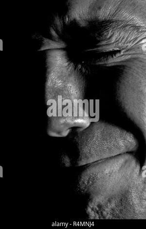 close up black and white male pained facial expression - Stock Photo