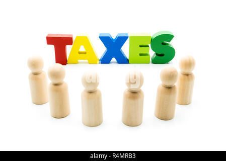 Wooden figures posing as business men in front of the word TAXES, high key isolated on white. - Stock Photo