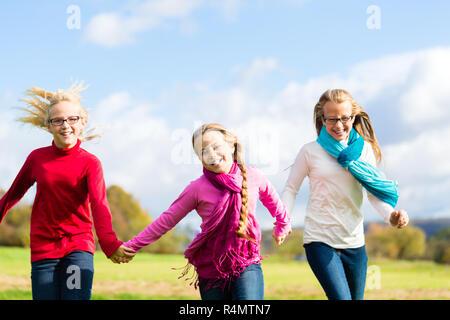 Girls running through fall or autumn park - Stock Photo