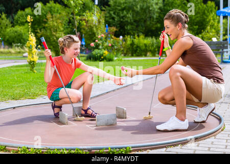 Family playing miniature golf in summer - Stock Photo