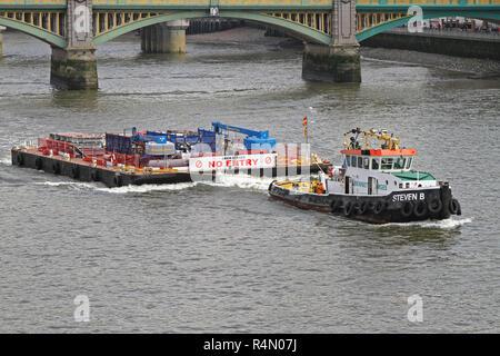 LONDON, UNITED KINGDOM - APRIL 09: Tugboat and Barge at Thames in London on APRIL 09, 2010. Tug Pulling Construction Platform Near Blackfriars Bridge  - Stock Photo