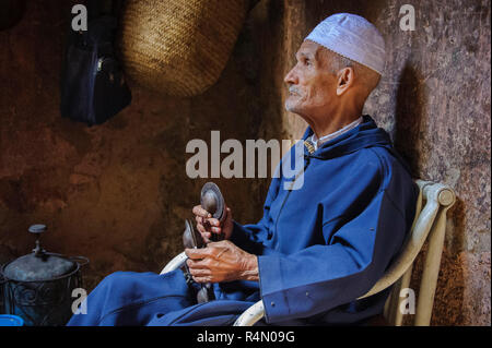 18-04-11. Marrakech, Morocco.  An elderly man dressed in traditional clothes and a skull cap, plays krakebs,  large iron castanet-like musical instrum - Stock Photo