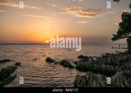 Colorful sunset over the Adriatic Sea, viewed from the croatian coast near Zadar. The croatian coast is famous for warmth, nature and it's sunsets. - Stock Photo