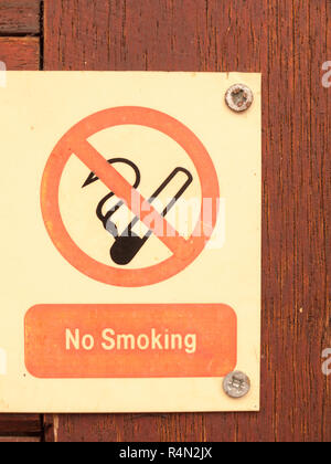 a nailed and screwed down sign red and black and white saying no smoking with a circle crossed of a cig cigarette no allowed safety health private restrictions - Stock Photo