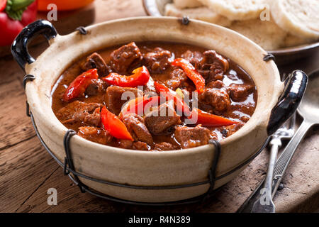 A bowl of delicious authentic Hungarian goulash with bread dumplings and red pepper garnish. - Stock Photo