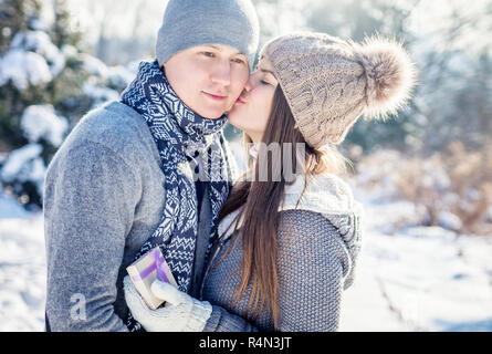 Girl kisses her boyfriend for a gift on Valentine's day - Stock Photo