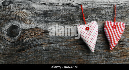 two white-red fabric hearts on a dark wooden background in size 18: 9 - Stock Photo