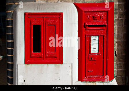 A wall mounted  Victorian post box alongside an unused Type E stamp vending machine at Lowestoft Railway Station in Suffolk, UK - Stock Photo