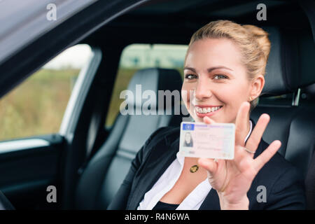 Woman showing her driving license out of car - Stock Photo