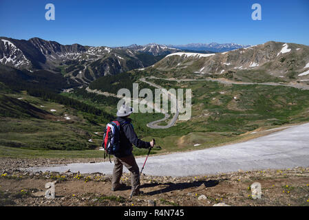 Hiker looking at view of mountains at Loveland Pass in Colorado - Stock Photo