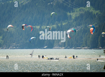 Kite boarders stand on an sand bar near Squamish Terminals.  An extra low tide exposed the normally submerged sand bar.  Saturday, May 27, 2017.  Phot - Stock Photo