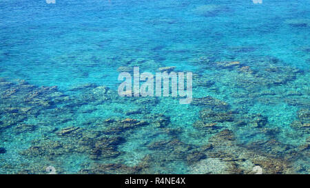 crystal clear blue sea surface with stone bottom, sea background, water texture - Stock Photo