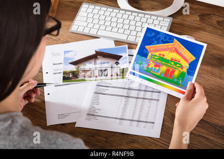 Person Analyzing The Heat Loss Of A House - Stock Photo